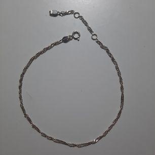 Väldigt fin fotlänk i silver, tror jag köpte den för 149 kr. Sparsamt använd. Ca 22.5 cm till den första öglan och hela kedjan är ca 27 cm. Frakt 11 kr. Se min profil för fler smycken.