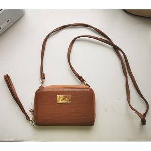 Liten brun väska, axelbandet och det lilla bandet går att ta av så fungerar också som en plånbok, den har några mindre skador på baksidan (se bild 3) 50kr + frakt 22kr