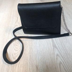 En svart läderväska (fakeläder) med silverkedja. Använt många gånger men fortfarande i fint skick
