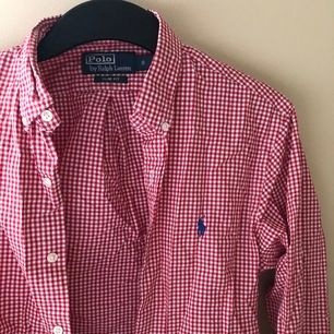"""En vit/röd rutig rherrskjorta från Polo Ralph Lauren. Storlek S, sitter lite oversized på mig som bär """"S dam"""". Köpt för 1250 kr, frakt ingår. Högstbudande får sen om flera är vid intresse. Endast använd 1 gång!"""