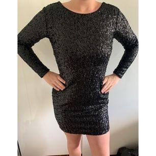 Här kommer de en till svart paljettklänning med öppen rygg. Den här är långärmad som kanske kan kännas lite mer bekväm. Aldrig använd!! Kort i modellen, dragkedja finns på baksidan av klänningen.