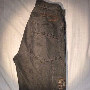 Brun/gråa design jeans med detaljer på bakfickan . Längd från midja till slutet är 103 cm och midjan är 35.5 cm (kontakta för fler bilder eller info)
