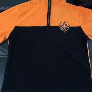 Orange zip-up fleece i bra skick. Köparen står för frakt