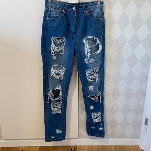 Blåa jeans med slitningar på benen. Väl använda men i bra skick