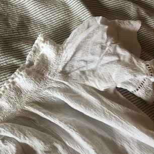 Fin vit blus med detaljer på ärmarna, offshoulder, använt en gång