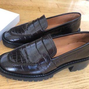 Säljer ett par helt oanvända loafers från & Other Stories. Dom är i mörkbrunt skinn med lite platå. Säljer pga att jag köpte dom sista i en storlek för små, 36. Nypris är 990kr