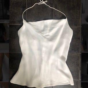 Vitt linne i sidenmaterial. Draperad urringning och den knyts i nacken. Knappt använd. Från Zara