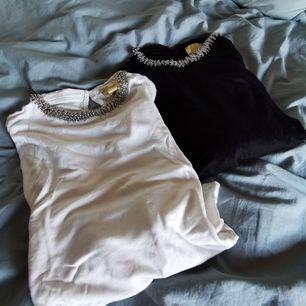 en vit och svart tishört med pärlor runt halsen, små I storlek 1=180 2=300           🍭fri frakt