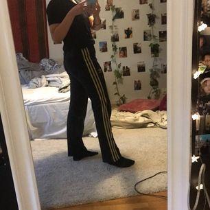 Ett par svarta mid waist adidas byxor med gulliga sträck, köpte på humana för några månader sen men dom är knappt andvända.