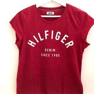 Röd Tommy Hilfiger T-shirt i storlek S. Mycket gott skick. Något croppad modell med avklippta sömmar nedtill och vid ärmar.