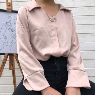 sparsamt använd ljusrosa blus i silkes-liknande material med gulddetalj & vida ärmar. storlek s men passar även större/mindre beroende på hur du vill att den ska sitta! modellen är 164 cm lång.