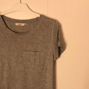 grå tshirt med sydda detaljer och ficka. säljer för 20kr + frakt