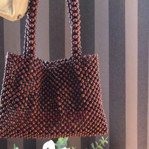 Säljer min söta lilla väska från Na-Kd, den är gjord av träkulor (typ), helt ny har kvar lapparna tillomed tror jag, runt 500 nypris💜💞
