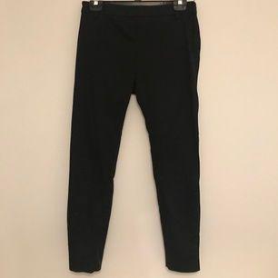 Svarta kostymbyxor i storlek 38. Säljer pga att de är förstora i midjan. Det finns en dragkedja i vänster sida där man knäpper byxorna. Köparen står för frakt.