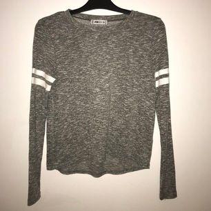 En vanlig grå tröja med vita band runt armarna. Den är stickad fast väldigt smått (se sista bild). Storlek XS men passar även S. Köparen står för frakt.