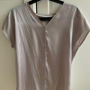 Supersnygg blus i sidenliknande tyg framtill och vanligt t-shirt tyg baktill. V-ringad och söm i fram! Klassisk och stilren🤩 Väldigt fint skick.