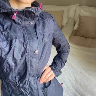 """Marinblå jacka från Abercrombie and fitch med rosa detaljer . Det är en tunn """"prasslig"""" vindjacka. Tål lite duggregn. Två fickor, luva och resår i midjan. Nypris över 600kr, nyskick. Finns i Stockholm eller skickas mot frakt❣️"""