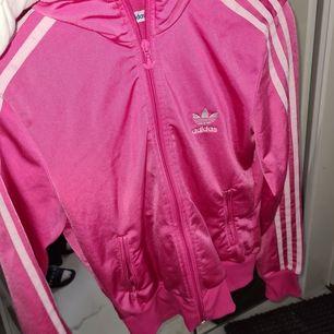 Det är en rosa Adidas kofta i storlek 38 som är använd fåtal gånger😊