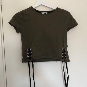 Mörkare grön cropped t-shirt med snören på sidorna💚 Den är i storleken XS och jag säljer den för 30kr + frakt.