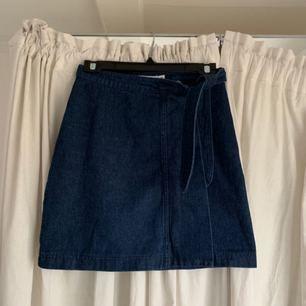 Så fin jeanskjol ifrån Na-Kd. Mörkblå kjol med knytband som försluts med dragkedja. I väldigt gott skick!!  Köparen står för frakten!!