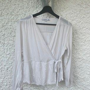 En vit långärmad tröja med v ringning, även med ett knyte på sidad som en gullig detalj som går att knyta om. Använd ett få tal gånger och i fint skick.