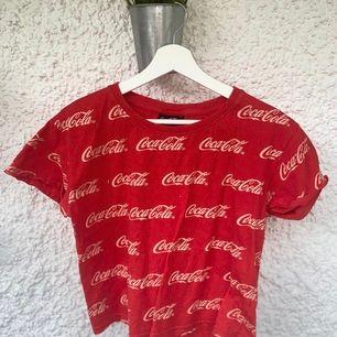 En röd T-shirt med CocaCola märket över hela, både fram och bak.