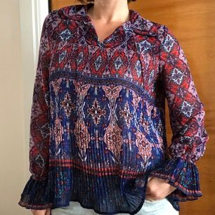 Kul och färgglad blus i polyester med plisserat tyg. Bred och luftig modell. Gott skick. Frakt tillkommer 40kr