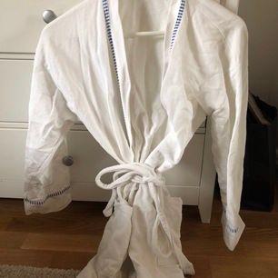 Vit morgonrock med tunna blå sträck på ärmarna t.ex. Mycket fint skick. Strl S.