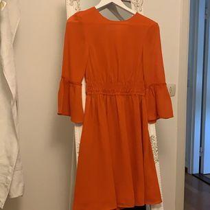 En orangeröd klänning från H&M i storlek XS. Använd fåtal gånger, skriv för mer info.