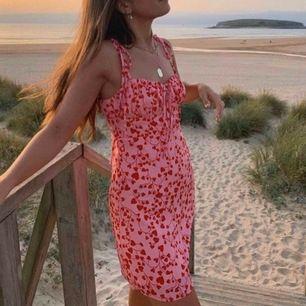 Rosa klänning med rött mönster från Loavies i storlek S, så fin till sommaren!! Lånad första bild, egen andra bild. Spårbar frakt på 63 kr tillkommer, alternativt att du hämtar upp klänningen hos mig i Bromma. 💕💕💕💕