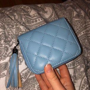 Blå plånbok med brun färg inuti.