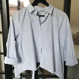 Superfin blå/vit skjorta som är croppad i ryggen med ett knyte. Aldrig använd och inköpt på pull&bear. Storlek S men väldigt flott fit så passar troligen XS-M.