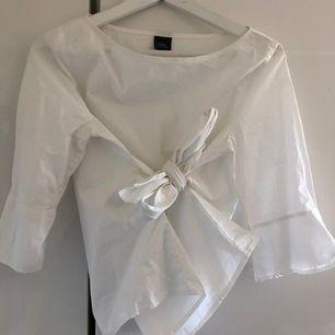Helt ny vit blus från Iora. Stl 38, (passar stl S & M). Knyts där fram eller bak, går att välja själv. Skickas mot fraktkostnad 44 kr.