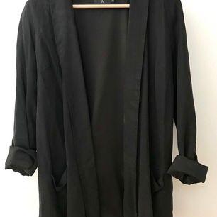 Lite oversize svart, mockainspirerad kavaj i mjukt tyg (Tencel). Uppkavlade armar på bilden. Snygg till ett par slitna jeans.