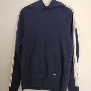 Blå hoddie från GANT. Storlek M. Knappt använd. Köparen står för frakten.