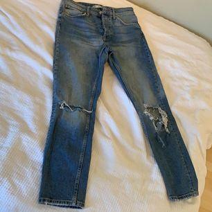 Blå jeans med knappar och slitningar och är högmidjade.