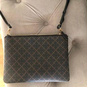 fin Marlene Birger väska som går att hänga som en axelremsväska då den har långa band, men går även att ta av bandet och ha den som en clutch! Rosa insida och väldigt fint skick då den är ganska ny och använd bara ett par gånger. Guldig dragkedja.