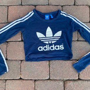 Cool mörkblå adidas croppad tröja! De klassiska tre strecken på ärmarna!