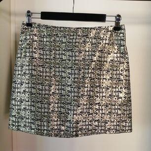 H&M mini kjol i guld och svart mönster. A-line, regular fit, medium high waist. Size 38.