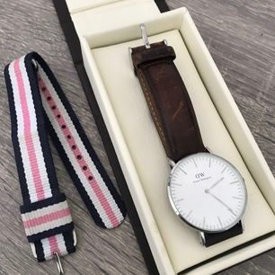 en dam Daniel Wellington klocka 36 mm i silver. i priset ingår klockan med både det bruna läderbandet och det randiga tygbandet! allt med silverdetaljer. saknar kvitto men kan garantera 100% äkthet.