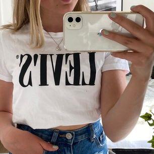 """Detta är en vit Levis te-shirt med en """"levi's"""" tryck på i svart. Den har aldrig varit använd och är i mycket fint skick:)"""