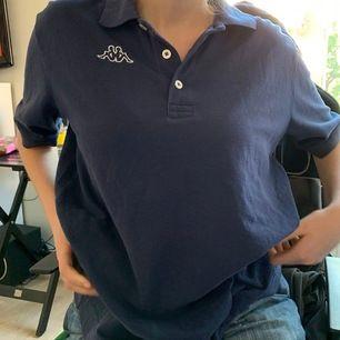 Nice mörkblå piké från kappa med vita motiv. Det på framsidan är brodyr och bak under kragen är tryck. Fint skick. Sitter så här på mig med S :)