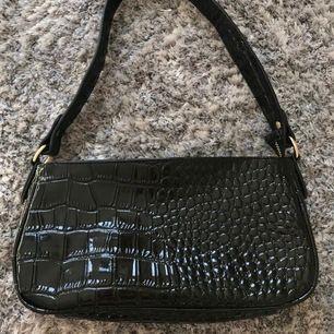 Fin svart liten väska i ormskinnsliknande material. Helt oanvänd så därmed i väldigt fint skick