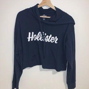 En croppad Hollister hoodie i marinblå färg, den har ett tunt svalt typ som är perfekt för sommaren! Säljer då det inte är min stil längre.