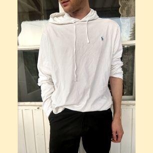 Tunn vit bomulls t-shirt med långa ärmar och luva. Märke: Ralph Lauren. Stl: xl. Köpt second hand på Roskilde festivalen, inte sliten alls pga väldigt fin när jag köpte den, och jag har endast använt ett par gånger.