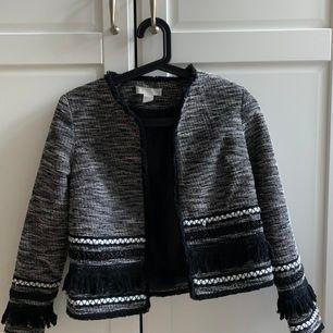 Supersnygg kavaj / blazer från H&M trend i svart och vit färg med fransar. Storlek 34, passar XS eller små S. Bra skick.  Chanel-inspirerad💫  Hämtas i Lund eller postas mot fraktkostnad.