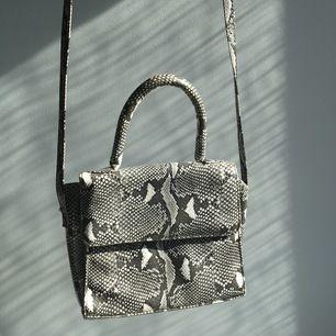 Väska med handtag + axelrem. Väskan är i ett läderliknande material med ormskinnsmönster