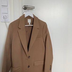 Jättefin beige kappa från hm som jag köpte i höstas men som tyvärr inte har kommit till användning så mycket. Jacka är i ny skick o frakten ingår i priset!