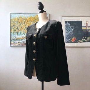 Vintage blazer i ett svart sammetsliknande tyg, med vackra knappar. Jag skulle säga att den kan passa en storlek 34-40 beroende på vilken passform som önskas. (Jag är storlek 36)