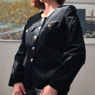 Vintage blazer i svart sammet, med vackra knappar. Jag skulle säga att den kan passa en storlek 34-40 beroende på vilken passform som önskas. (Jag är storlek 36)